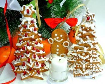 имбирные пряники в виде звездочек, политые глазурью и сложенные в форме елочки на столе, рядом свеча и мандарины