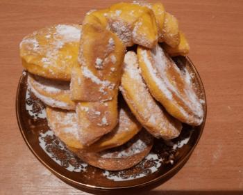 на блюдце горкой лежа пряники из тыквы, присыпанные сахарной пудрой