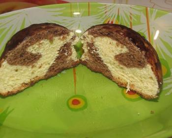 разрезанный пополам пряник зебра, политый шоколадом, на зеленой тарелке