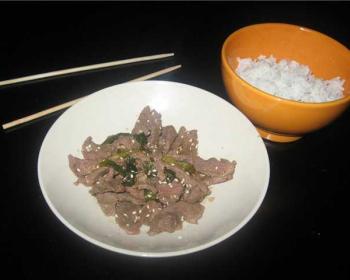 пульгоги из говядины с зеленым луком и семенами кунжута в белой тарелке, рядом на столе лежат китайские палочки и отварной рис в оранжевой пиале