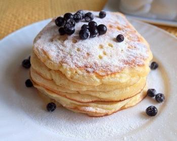 пышные оладьи, сложенные друг на друга и присыпанные сахарной пудрой, на белой плоской тарелке с черничными ягодками, на столе, застеленном скатертью