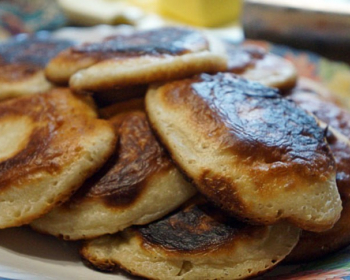 готовые пышные оладьи на сметане в тарелке на столе