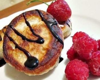 три жареные оладьи, политые вареньем, ягоды малины на белой плоской тарелке