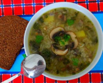 рассольник с грибами в тарелке с ложкой, кусочек черного хлеба на столе, застеленном скатертью