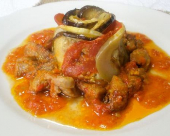 рататуй с кусочками мяса, кабачками, помидорами и баклажанами, политый подливой, на белой плоской тарелке