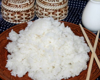 вареный рис на коричневой плоской тарелке с китайскими палочками на столе, покрытом скатертью