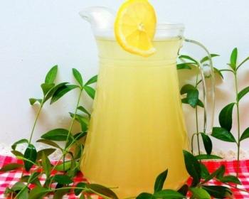 квас из риса в стеклянном фужере с ломтиком лимона на столе, прикрытом полотенцем, рядом зеленые листики