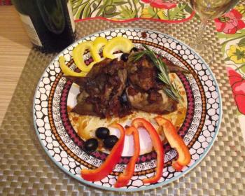 жареный рябчик в тарелке в сочетании с нарезанным желтым и красным болгарскими перцами, трема маслинами и веточкой розмарина