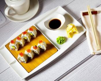 роллы филадельфия из отварного риса и сыра с красной икрой на белой тарелке с соевым соусом на столе, рядом китайские палочки