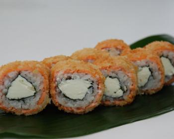 роллы из вареного риса, красной рыбы, огурца и сыра на зеленом листе