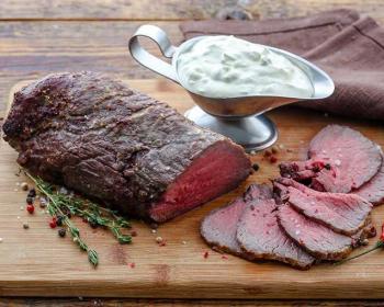 целый и нарезанный ломтиками ростбиф из говядины лежит на деревянной разделочной доске, рядом металлическая соусница с соусом