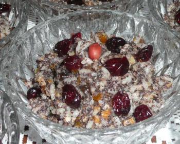 рождественская кутья с гречишным медом, изюмом, маком и измельченными орехами, сверху присыпанная ягодами клюквы, в прозрачной пиале на столе