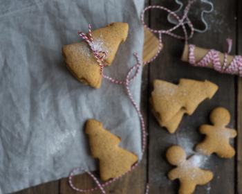 на столе и на кусочке ткани лежат рождественские пряники в виде елочек и человечков, несколько пряников-елочек лежат стопкой, связанные красной тесемкой