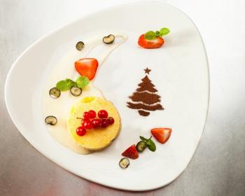 желтый круглый рождественский пудинг, веточка красной смородины, елочка из какао-порошка, дольки клубники, листочки мяты, сгущенное молоко на белой тарелке, на столе