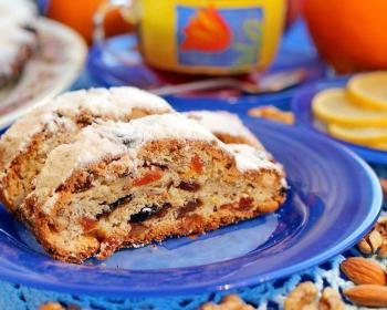 на круглой синей тарелке лежат два кусочка рождественского штоллена с сухофруктами, присыпанных сахарной пудрой