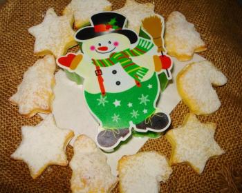 рождественское печенье в форме звездочек и елочек на тканевом мешке с фигуркой снеговика