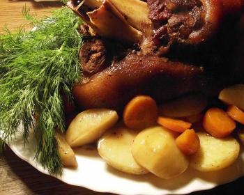 запеченная свиная рулька на тарелке с картофелем, морковью, пучком свежего укропа