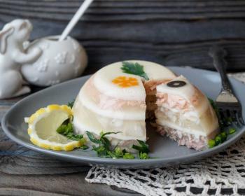 красивое рыбное заливное на широкой белой тарелке на столе, украшенное свежей зеленью и лимоном, на фоне стоит белая солонка в форме зайца