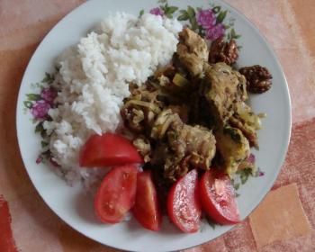 сациви с кусочками курицы, вареным рисом и нарезанными помидорами на белой тарелке на столе, застеленном скатертью