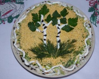 слоеный салат из курицы и чернослива, украшенный зеленью и майонезом в виде березок, на тарелке на столе