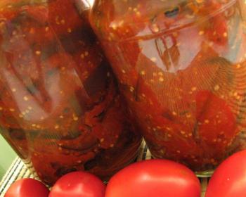 две стеклянных банки с салатом Десятка на столе, на фоне свежие помидоры