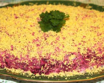 слоеный салат из форели, свеклы, яиц и майонеза, украшенный веточками петрушки, в салатнице на столе