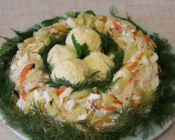 салат гнездо глухаря с яйцами, жареной картошкой и морковью, перемешанный с майонезом и украшенный рубленым укропом, на тарелке на столе