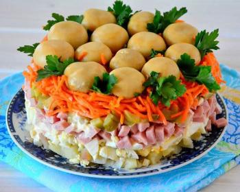 слоеный салат Грибная поляна с ветчиной, украшенный маринованными шампиньонами и свежими листочками петрушки