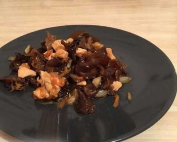 салат из китайских древесных грибов с куриным филе, овощами, специями и соевым соусом на черной тарелке на кухонном столе