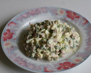 салат из кусочков кальмаров, яиц и зеленого лука, перемешанный майонезом, на плоской тарелке на столе