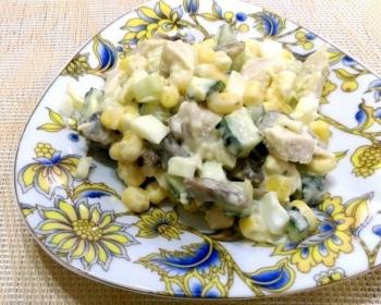 салат с кусочками курицы, грибов, свежих огурцов и вареными яйцами, заправленный майонезом, на белой плоской тарелке с цветочками на столе, застеленном деревянным ковриком