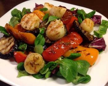 салат из морских гребешков, болгарского перца, баклажанов и свежей зелени на белой круглой тарелке