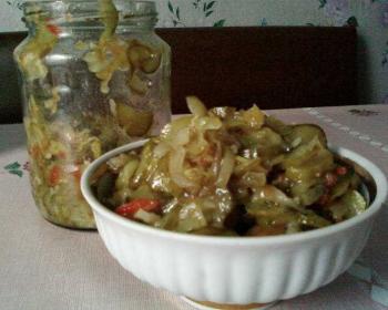 салат из огурцов по-корейски, лук полукольцами, красный перец в растительном масле, в белой тарелке на столе, банка с салатом рядом на столе