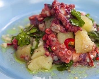 салат с кусочками осьминога, картошки, помидоров и петрушки на голубой плоской тарелке