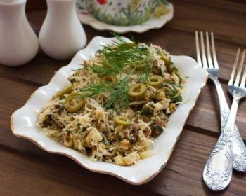 салат из сайры консервированной, украшенный тертым сыром, кружочками оливок и укропом