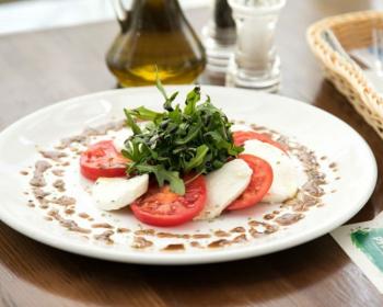 белая широкая тарелка с салатом Капрезе, украшенным свежей зеленью, рядом стоит бутылочка с маслом