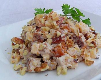 салат Клеопатра из куриного филе, твердого сыра, грецких орехов и сухариков на белой квадратной тарелке, украшенный веточкой петрушки