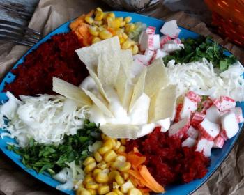 салат из тертой сырой свеклы и моркови, измельченной белокочанной капусты, нарезанных крабовых палочек, рубленой зелени и консервированной кукурузы, заправленный майонезом, сверху выложены чипсы, на синей плоской тарелке на столе