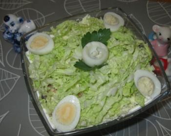 слоеный салат лебединый пух с пекинской капустой и куриными яйцами, украшенный листиками петрушки, в стеклянной миске на столе