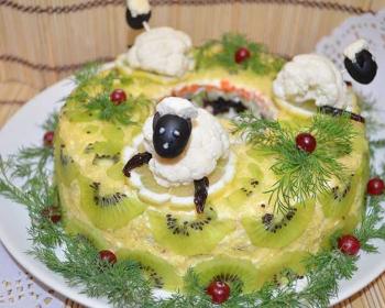 салат Малахитовый браслет, украшенный дольками киви, ягодами клюквы и зеленью укропа, сверху на салате три овечки из цветной капусты и чернослива