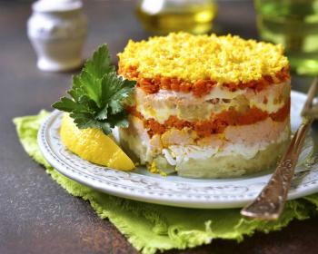 слоеный салат Мимоза классический с сыром на белой тарелке, рядом лежит вилка, долька лимона и веточка петрушки