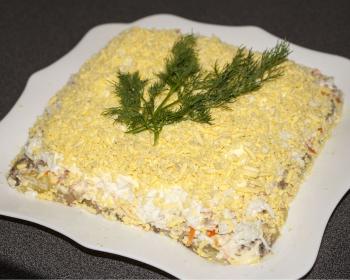 слоеный салат Мимоза с картошкой и рыбной консервой в квадратной тарелке на столе