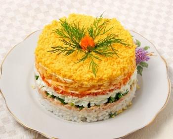 слоеный салат мимоза из вареного риса, рыбной консервы, яиц, моркови и сыра, пропитанный майонезом и украшенный веточками укропа, на белой плоской тарелке на столе, застеленном скатертью