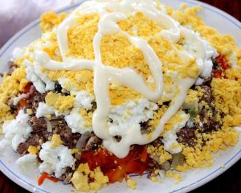слоеный салат Мимоза с сайрой лежит на большом белом блюде, сверху салат присыпан измельченными желтками и полит майонезом