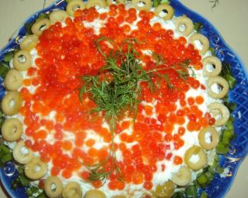слоеный салат морская жемчужина с оливками, красной икрой, майонезом и зеленым луком, украшенный веточками укропа, на плоской тарелке на столе