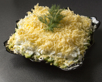 салат Нежность с курицей и черносливом в квадратной тарелке на столе