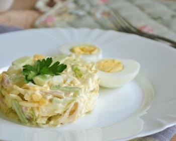 на белой круглой тарелке порция нежного салата с ветчиной, сверху листок петрушки, рядом яйцо, разрезанное пополам