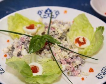 ну белой тарелке с узорами лежит салат оливье классический, возле салата лежат три маленьких листа молодой капусты, внутри которых лежат половинки перепелиных яиц с икрой, две веточки зеленого лука и веточка базилика лежат сверху на салате