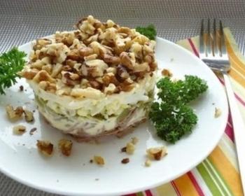 слоеный салат Принц с говядиной и свежей зеленью на широкой белой тарелке на столе, рядом лежит вилка