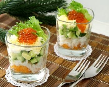 слоеный салат из кусочков рыбы, авокадо, вареного риса и красной икры, украшенные листиками салата, в двух разных стеклянных